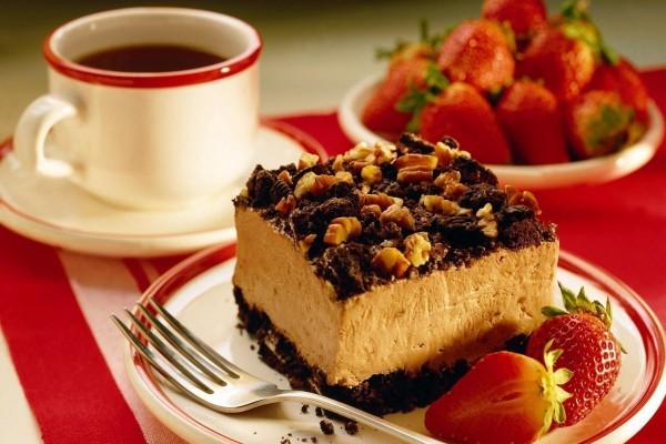 Pastel con frutos secos, fresas y una taza de café
