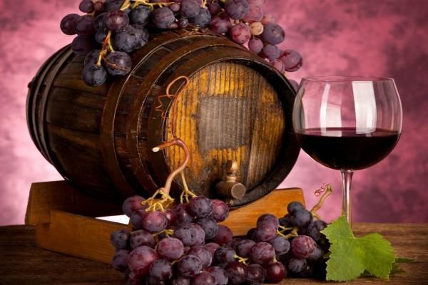Un barril, una copa de vino y unos racimos de uvas moradas