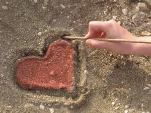 Postal: Dibujando un corazón en la arena