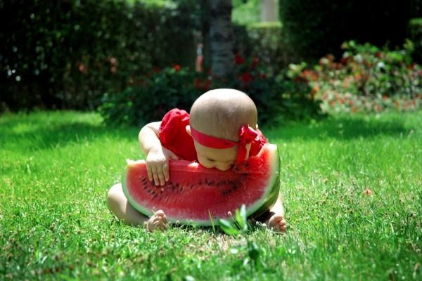 Precioso bebé queriendo comer sandía