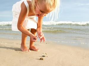 Postal: Niña recogiendo conchas en la playa