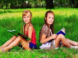 Postal: Niñas leyendo sus libros en el parque