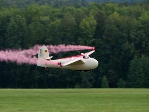 Postal: Avioneta despidiendo humo rosa