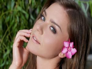 Modelo con una flor rosa en la oreja