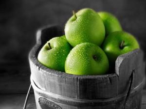 Un cubo de madera con manzanas verdes