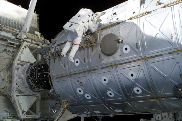 Astronauta realizando trabajos sobre un satélite