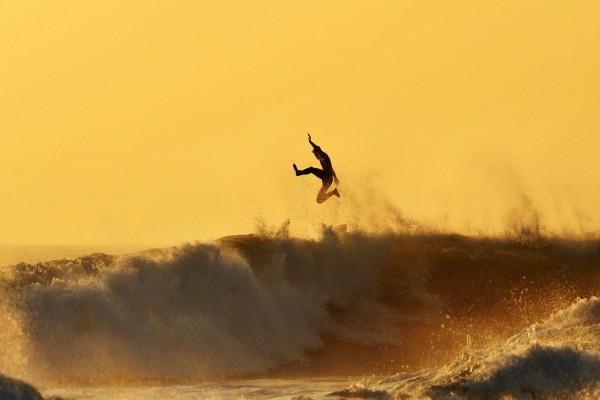 Practicando surf a la puesta del sol