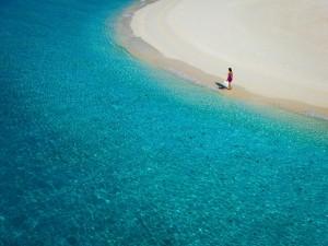 Postal: Una mujer paseando por una bonita playa