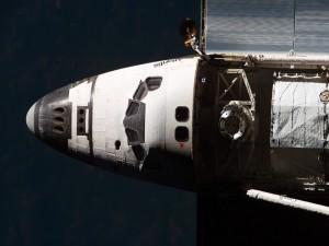 Postal: El transbordador Atlantis transportando un satélite