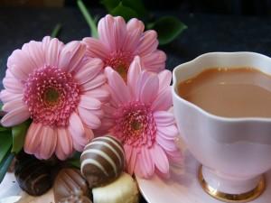 Postal: Té con leche, bombones y flores