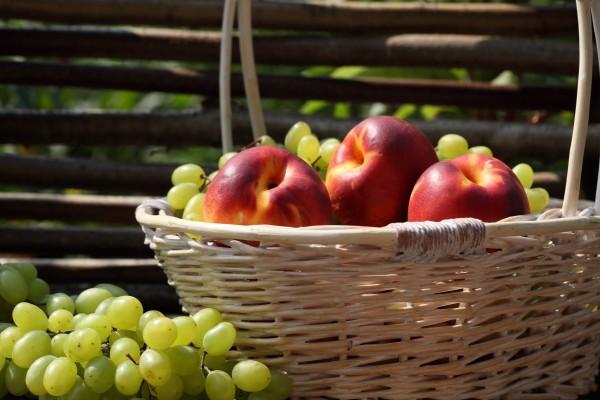Cesta con melocotones y uvas