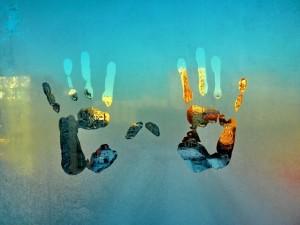 Postal: Huellas de manos en un vidrio