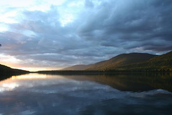 La luz del sol y las nubes reflejadas en el lago