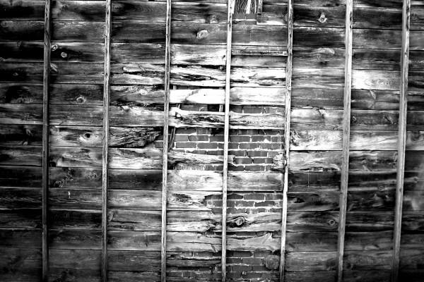 Tablones cubriendo una pared de ladrillos