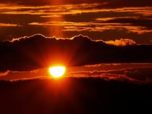 Postal: El sol entre dos grandes nubes