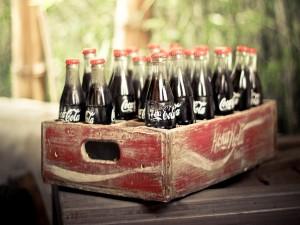 Postal: Botellas de Coca-Cola en una vieja caja de madera