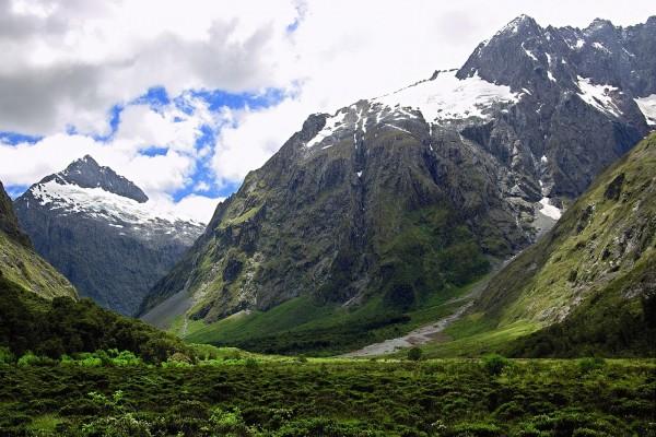 Montañas verdes con nieve en la cima