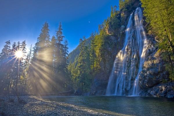 Rayos del sol iluminando una cascada