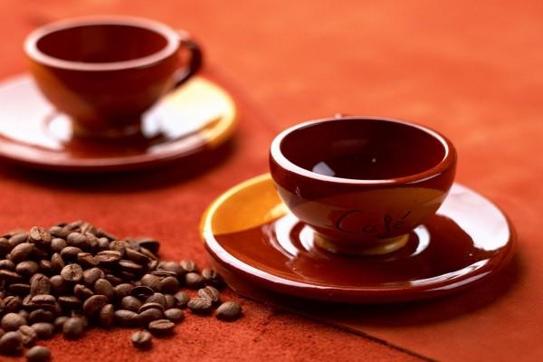 Dos tazas rojas y granos de café