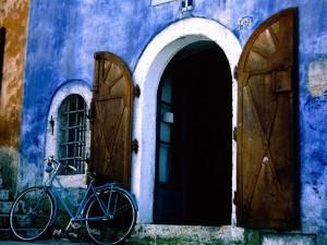 Postal: Bicicleta azul en la puerta de casa