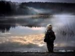 Niño mirando un lago en la noche