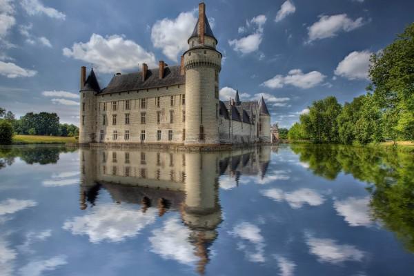 Castillo, nubes y árboles reflejados