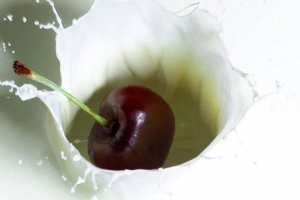 Una cereza cayendo en la leche