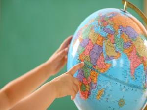 Postal: Manos sobre el globo terráqueo