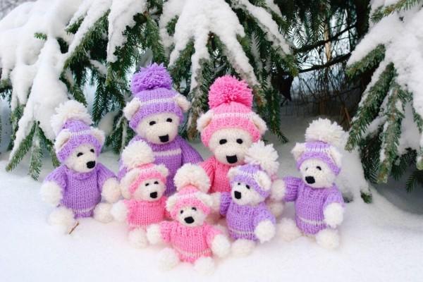 Familia de osos sentados al lado del arbolito de Navidad