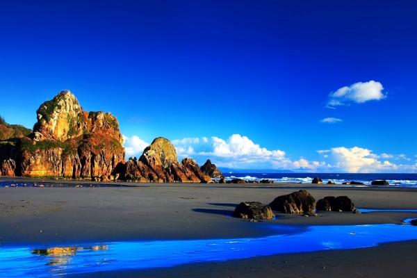 Playa con grandes rocas y un cielo azul