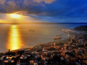 Postal: El sol iluminando el mar y los edificios