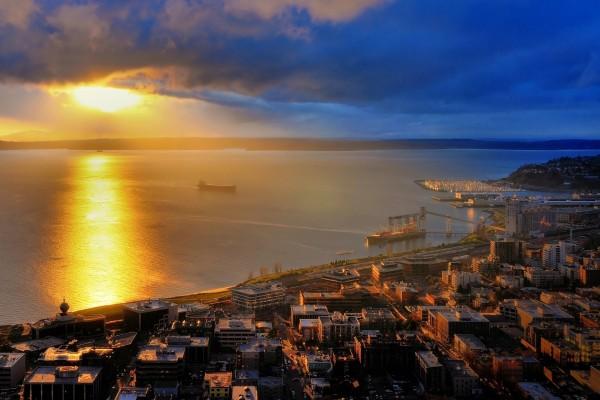 El sol iluminando el mar y los edificios