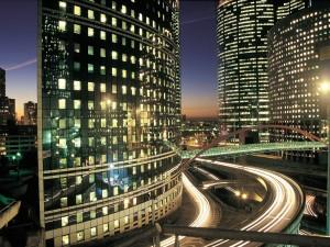 Postal: Carretera entre los edificios iluminados