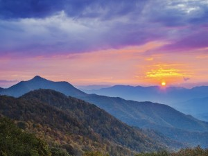 El sol asomándose entre nubes y montañas