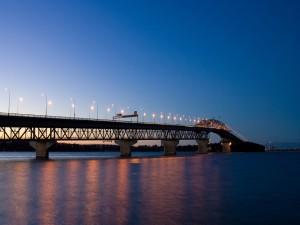 Postal: Un largo puente iluminado sobre el agua