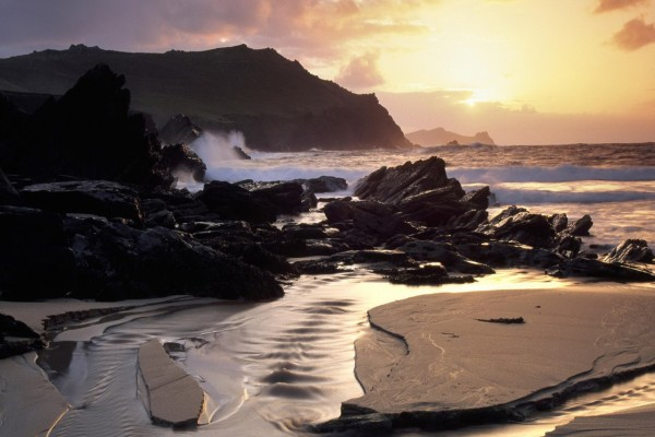 Arena mojada y grandes piedras en la playa
