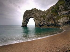 Playa con un arco en la roca