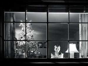 Postal: Niña mirando por la ventana la noche de Navidad