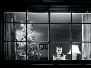Niña mirando por la ventana la noche de Navidad