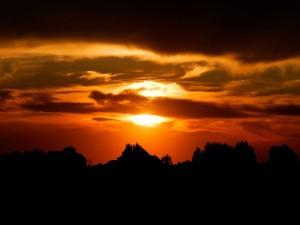 Postal: Cielo naranja y tierra en sombra