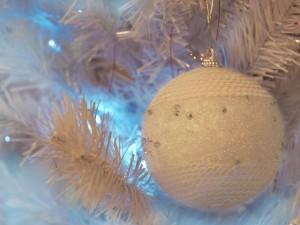 Postal: Delicada bola blanca colgada del árbol de Navidad
