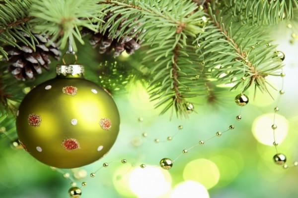 Bola verde colgada de la rama de un arbolito de Navidad