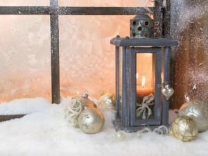 Farol con vela y bolas blancas frente a una ventana
