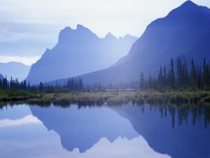 El sol iluminando las montañas y el lago