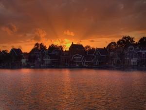 El sol detrás de las casas al atardecer