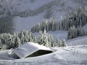 Cabaña cubierta de nieve cerca de la pista de esquí