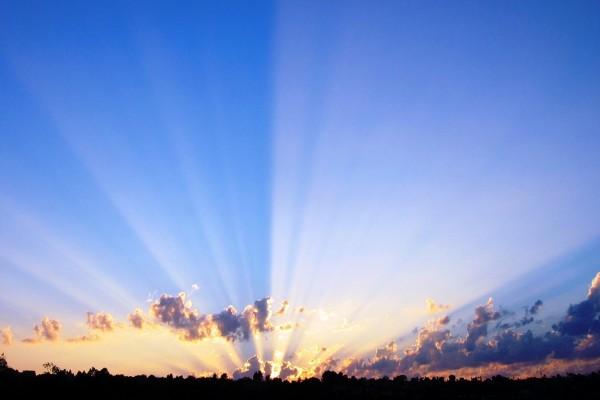 Largos rayos del sol en el cielo azul