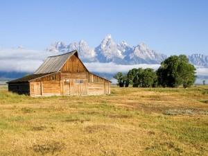 Postal: Granero de madera con las montañas de fondo