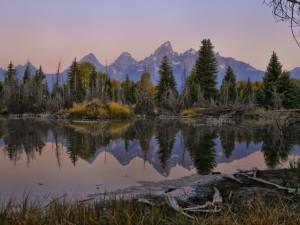 Árboles y montañas reflejadas en el lago al atardecer