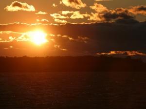 Postal: El sol y nubes en el cielo al atardecer